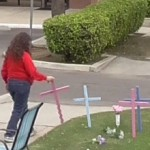 Terri puts a pink cross in the grass next to other crosses.